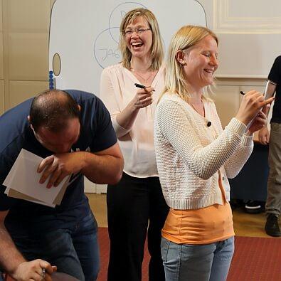 Kick-off med arbetsglädje - tre personer gör en övning en viker sig av skratt