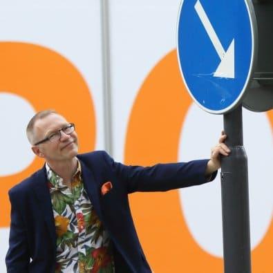 Tomas Eriksson håller i en stolpe med ett blått vägmärke med vit pil