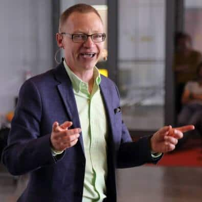 Föreläsaren Tomas Eriksson på scen ett konferensrum i ljusgrön skjorta pekandes utåt med båda pekfingrarna
