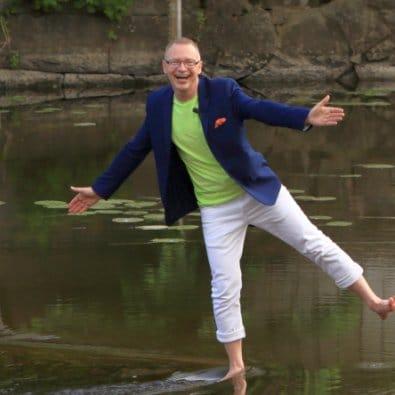 Föreläsaren Tomas Eriksson full av arbetsglädje på ett ben i en å