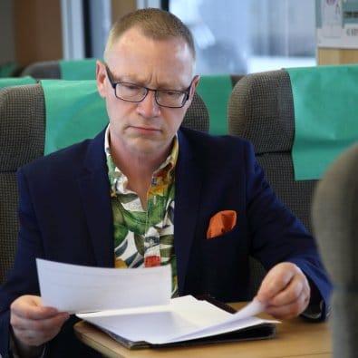 Föredrag Arbetsglädje - Tomas Eriksson tittar i sina papper sittandes på ett tåg