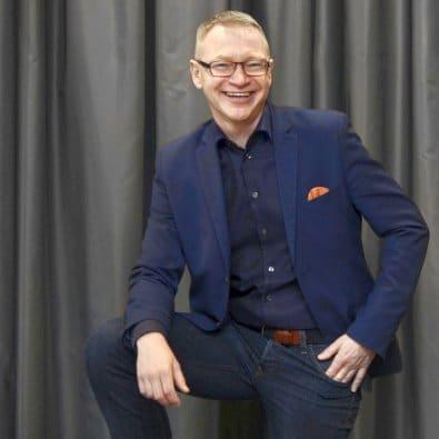 Tomas Eriksson föreläsare - på scen framför ett draperi
