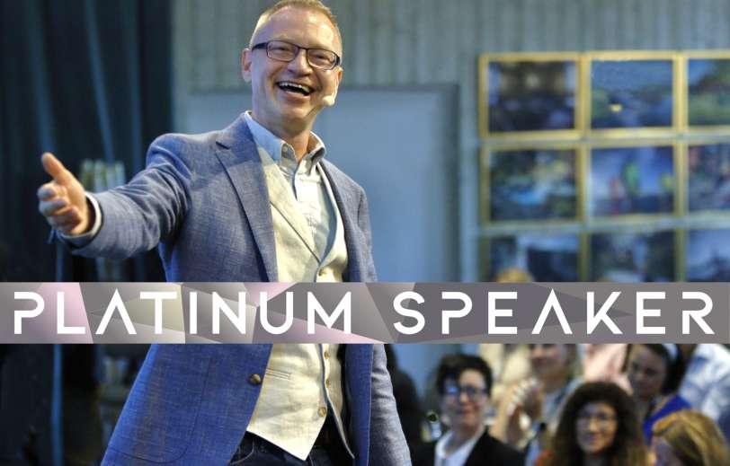 Föreläsare Tomas Eriksson på scen med stort leende och armen utsträckt - Platinum Speaker
