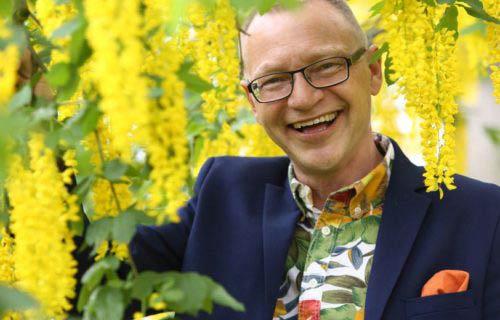 Föreläsare Arbetsglädje - Tomas Eriksson i mörkblå kavaj med stort leende omgiven av gult gullregn