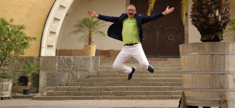 Föreläsaren Tomas Eriksson hoppar upp i luften med utsträckta armar framför en byggnad.