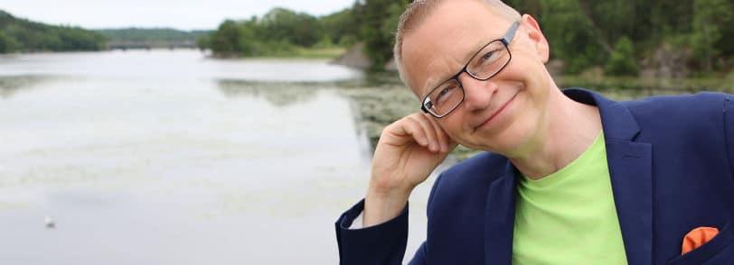 Tomas Eriksson - en föreläsare som lyssnar - här med huvudet lutande mot sin hand med vatten i bakgrunden.