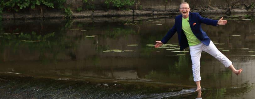 Föreläsaren Tomas Eriksson står på ett ben i en å med armarna utfällda