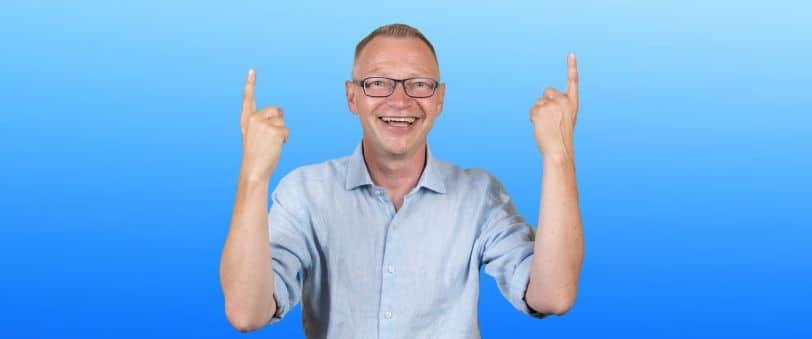 Föreläsare Tomas håller upp båda armarna och pekar uppåt.