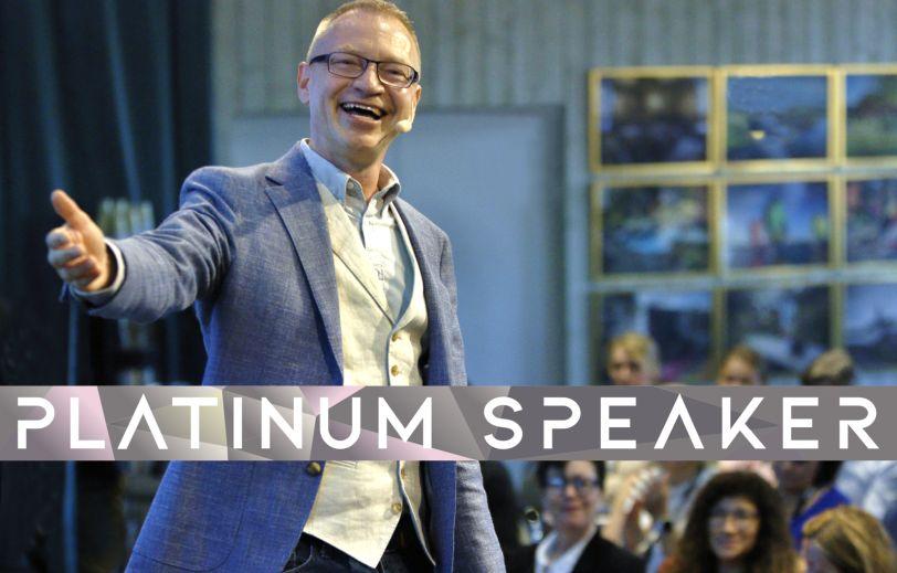 Föreläsare Tomas Eriksson på scen med en välkomnande hand utsträckt - Platinum Speaker
