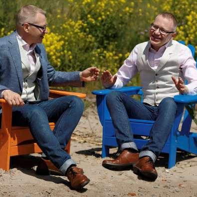 Föreläsaren Tomas Eriksson sitter i två stolar vid en sandstrand och ger feedback till sig själv