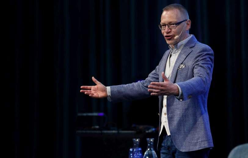 Föreläsare feedback - Tomas Eriksson pa scen i ljusblå kavaj med båda armarna utsträckta