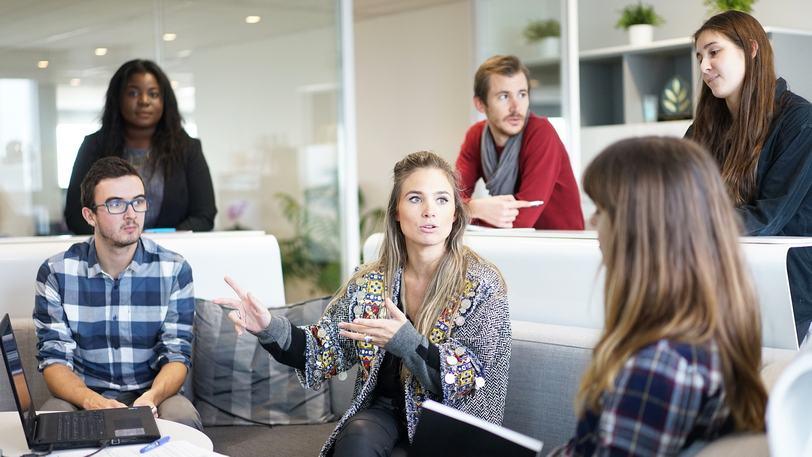 Chef i kontorsmiljö omgiven av medarbetare och kolleger