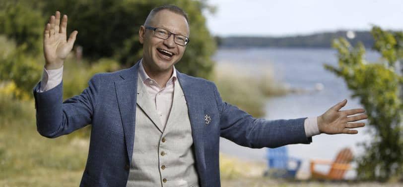 Föreläsare Tomas Eriksson med stort leende i kavaj och väst med grönska och stand i bakgrunden