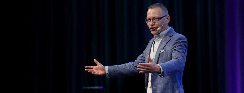Föreläsare Tomas Eriksson kommunicerar med utsträckta händerna på scen