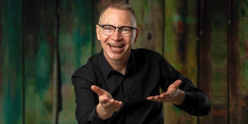 Inspirationsföreläsare Tomas Eriksson håller armarna utsträckta framför sig i en lyftande gest